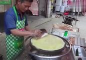 中国名吃煎饼果子,老板的手法干净利索,简单几步就把煎饼做好了