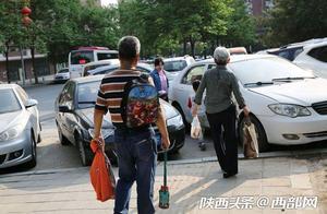 西安一人行道停车数年没人管 市民在车缝里艰难行路