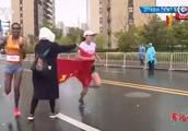 苏州马拉松争议一幕!中国选手冲刺争冠时刻,志愿者递国旗干扰