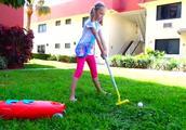 小萝莉在草坪上用不同颜色的高尔夫球杆打球
