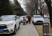 火爆的西安年人多车多 停车问题多草坪被碾压人行道被堵死